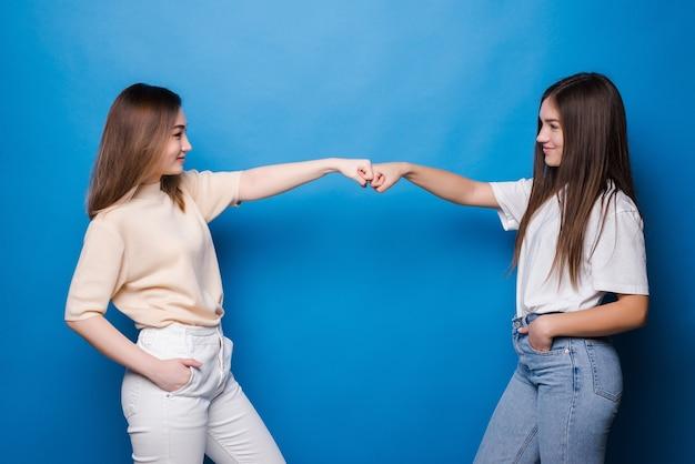 Due giovani donne felici con capelli diversi che danno il cinque a vicenda isolate sul muro blu