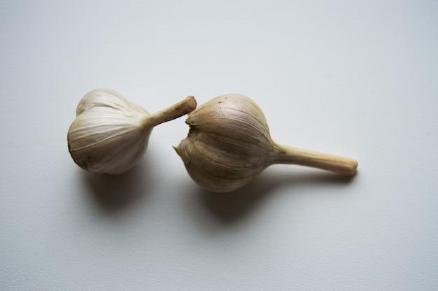Due teste d'aglio su sfondo chiaro