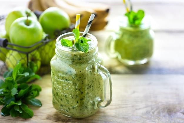 Due frullati verdi sani con spinaci, banana, mela e menta in barattolo di vetro.