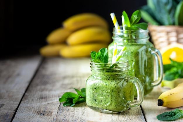 Due frullati verdi sani con spinaci, banana, arancia e menta in barattolo di vetro e ingredienti