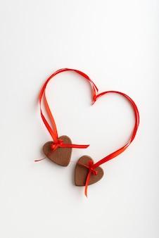 Due biscotti del cuore con nastri rossi su sfondo bianco.