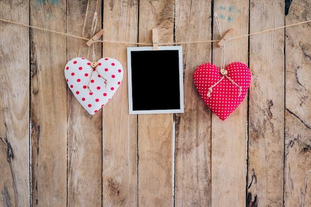 Due cuore e cornice fotografica appesa sulla corda clothesline con sfondo in legno.