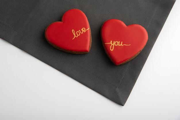 Due biscotti a forma di cuore con glassa di zucchero rosso su sfondo grigio e bianco. san valentino