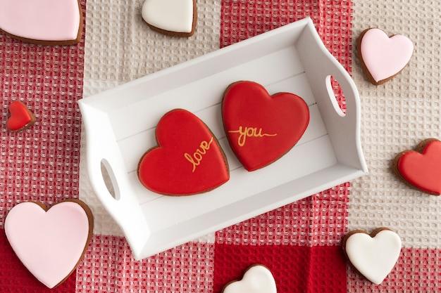 Due biscotti a forma di cuore con glassa di zucchero rossa sul vassoio in legno. san valentino trattare