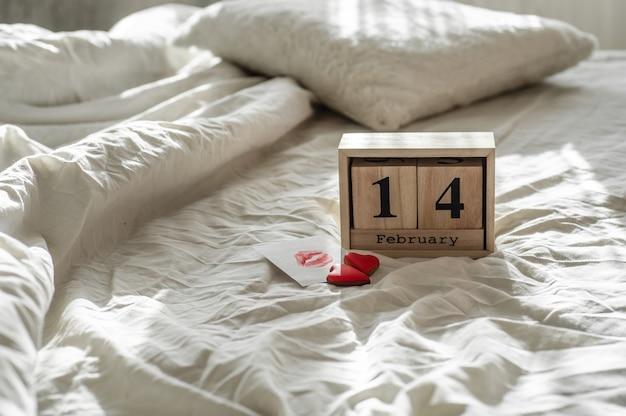 Due cuori di biscotti, una nota con un bacio con calendario in legno 14 febbraio su un letto bianco