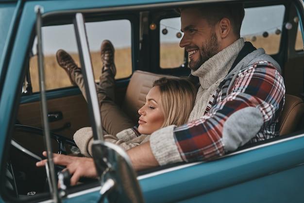 Due cuori pieni d'amore. attraente giovane donna che riposa tra le braccia del suo ragazzo mentre viaggia in mini furgone in stile retrò