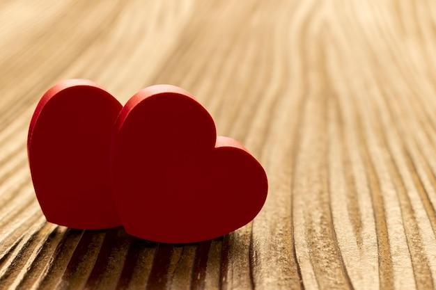 Due cuori insieme sul pavimento di legno rustico. san valentino.