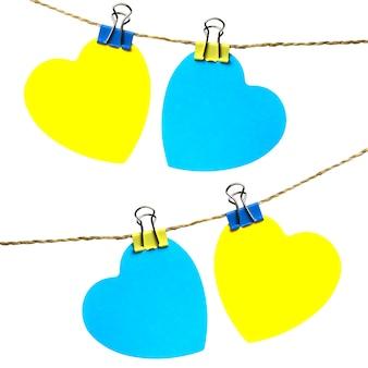 Due cuori gialli e blu che appendono su una corda con i rimorchi
