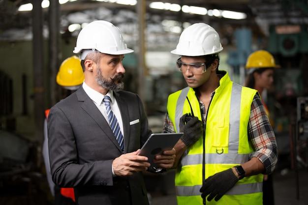 Due ingegneri dell'industria pesante stanno nella fabbrica di produzione, usano il computer tablet digitale, discutono.