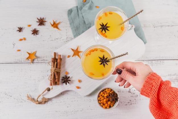 Due bicchieri alti con tè caldo colorato all'olivello spinoso con bastoncini di cannella, stelle di anice