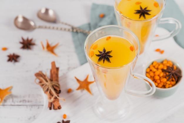 Due bicchieri alti con colorato tè caldo all'olivello spinoso con bastoncini di cannella