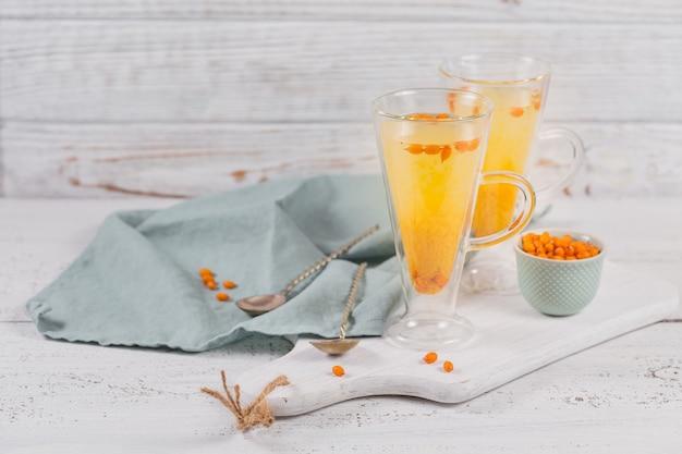 Due bicchieri alti con colorato tè caldo all'olivello spinoso con bacche fresche di olivello spinoso