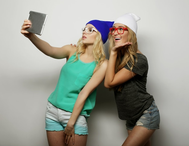Due amiche hipster che si fanno selfie con tavoletta digitale su grigio
