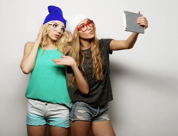Due amiche hipster che si fanno selfie con tavoletta digitale, studio girato su vackground grigio