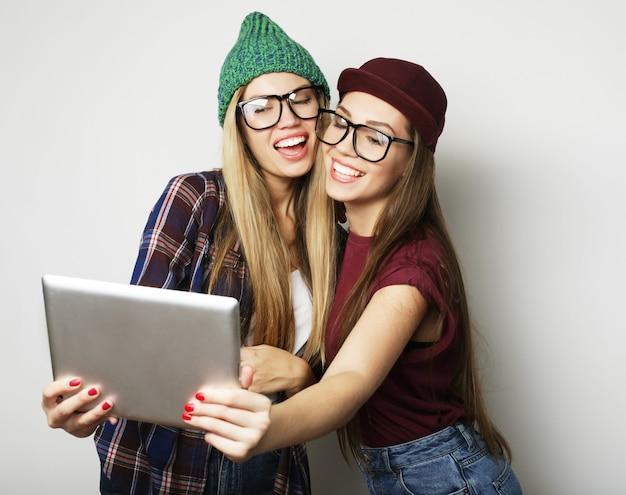 Due amiche hipster che si fanno selfie con tablet digitale, studio girato su sfondo grigio
