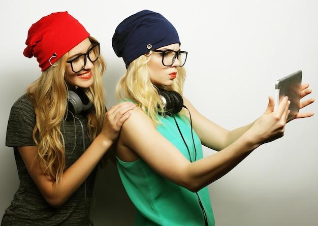 Due amici di ragazze hipster prendendo selfie con tavoletta digitale, studio colpo su grigio