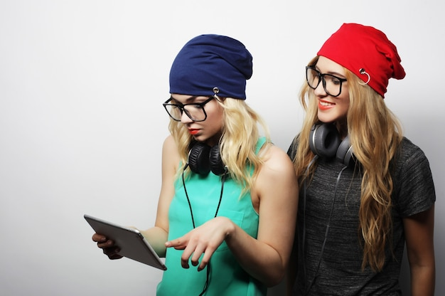 Due amiche hipster usano tablet digitale, studio girato su sfondo grigio