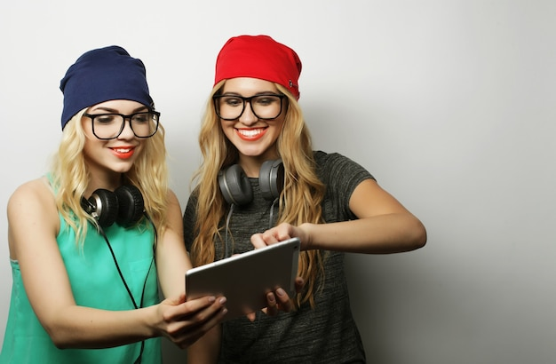 Due amiche hipster usano tablet digitale, studio girato su vackground grigio