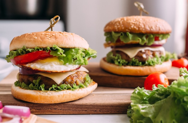 Due gustosi hamburger freschi fatti in casa con lattuga e formaggio. ingredienti in tavola. sfondo di cibo leggero.