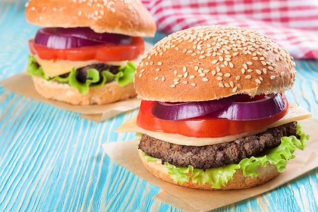 Due cheeseburger fatti in casa con polpette di manzo e insalata fresca su panini al mare, serviti sulla tavola di legno blu.