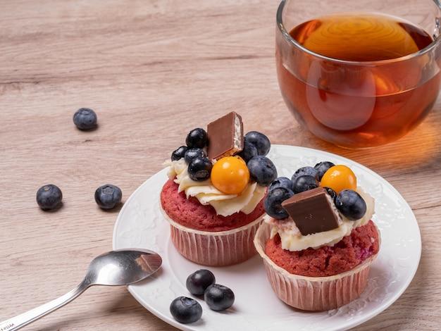 Due cupcakes alla frutta fatti in casa con cioccolato su un piatto bianco, una tazza di tè rotonda su un tavolo di legno. colazione a casa.