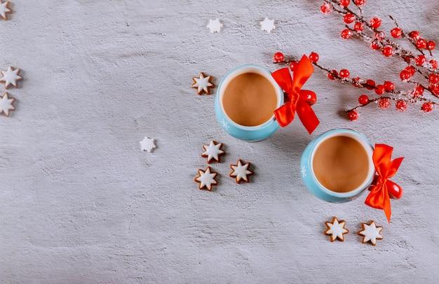 Due cacao caldo in tazze con la ciotola rossa, il biscotto a forma di stella e il ramo rosso della bacca su superficie bianca