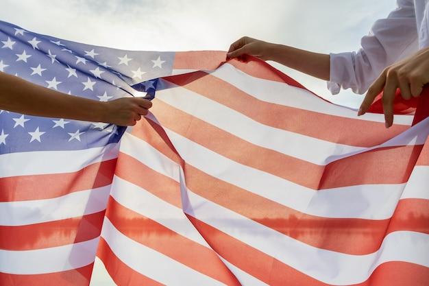 Due mani umane che tengono la bandiera nazionale degli stati uniti. celebrazione del concetto di festa dell'indipendenza degli stati uniti.