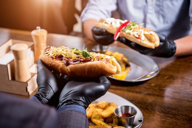 Due giovani affamati che mangiano hot dog in caffè. ristorante
