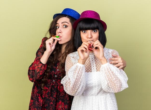 Due ragazze da festa impressionate che indossano un cappello da festa, entrambe suonano il corno della festa, una che mette la mano sulla spalla di un'altra ragazza isolata sul muro verde oliva