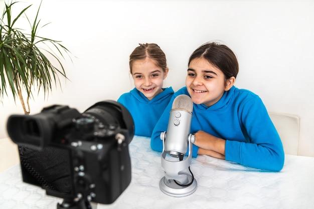 Due influencer sorelle e blogger che trasmettono in diretta dal loro salotto ridono e guardano la telecamera e parlano al microfono su un video o su una piattaforma di social network