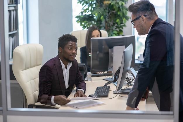 Due uomini d'affari interculturali che si consultano in ufficio