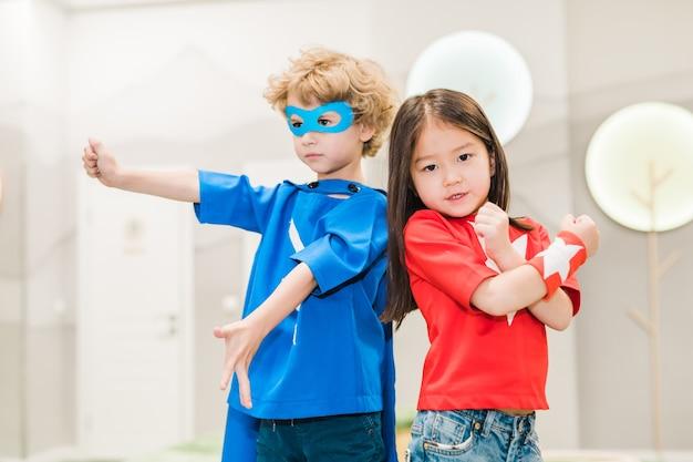 Due bambini interculturali in costumi di supereroi in piedi uno vicino all'altro davanti alla telecamera durante il gioco