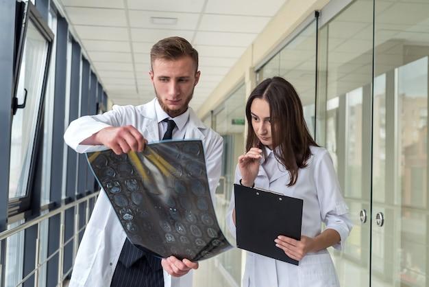 Due medici interni che esaminano la risonanza magnetica del cervello per il trattamento della lesione alla testa. concetto di salute
