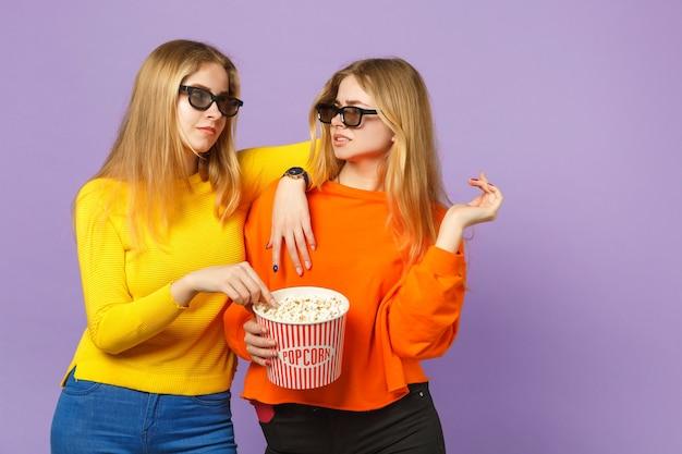 Due giovani sorelle gemelle bionde irritate in occhiali 3d imax che guardano film, tengono il popcorn isolato sulla parete blu viola pastello. concetto di stile di vita familiare di persone.