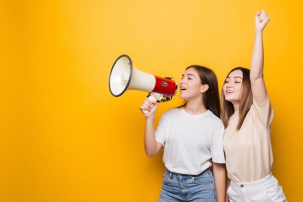 Due amiche irritate delle ragazze delle giovani donne urlano nel megafono isolato sulla parete gialla. persone concetto di stile di vita. mock up copia spazio.