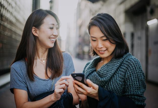Due donne giapponesi in giro a tokyo durante il giorno. fare shopping e divertirsi