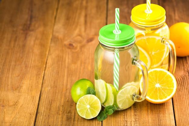 Due vasetti di acqua detox con fettine di arancia e lime