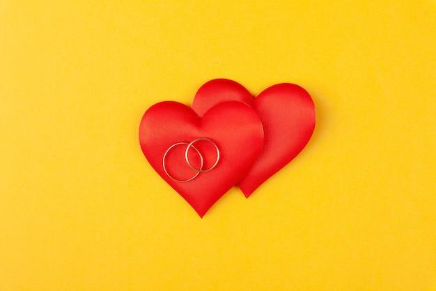 Due anelli d'oro rotondi gioiello su cuori rossi, concetto di amore, regalo, proposta di matrimonio