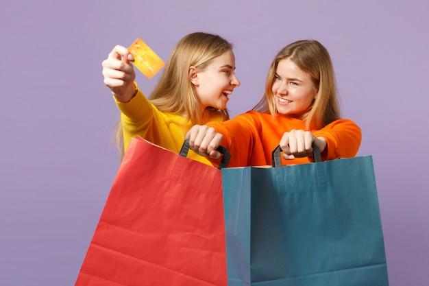 Due gioiose sorelle gemelle bionde ragazze in abiti vivaci che tengono la borsa del pacchetto della carta di credito con gli acquisti dopo lo shopping isolato sulla parete blu viola. concetto di famiglia di persone. .
