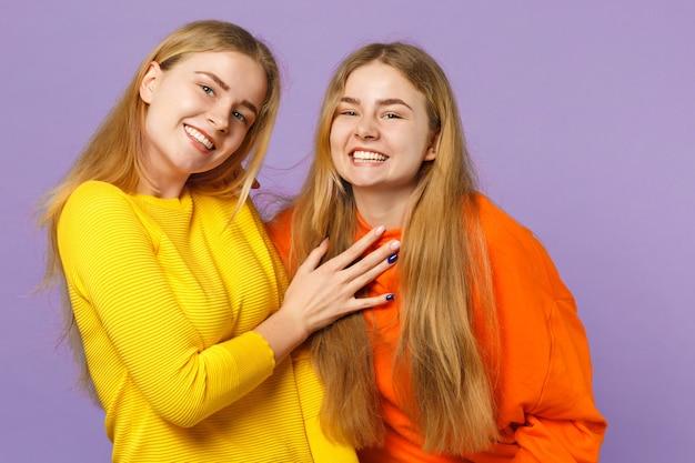 Due giovani sorelle gemelle bionde carine gioiose in abiti colorati vividi in piedi, isolate sulla parete blu viola pastello. concetto di stile di vita familiare di persone.