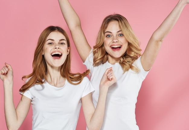 Due donne allegre in magliette bianche divertimento studio amicizia stile di vita. foto di alta qualità