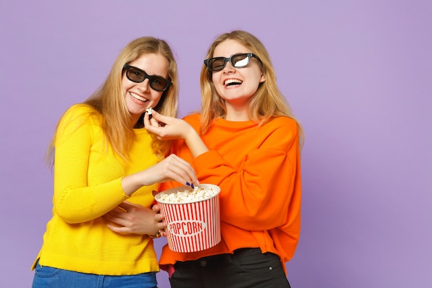 Due gioiose giovani gemelle bionde sorelle ragazze in occhiali 3d imax che guardano film, tenendo in mano popcorn isolato su parete blu viola pastello concetto di stile di vita familiare di persone.