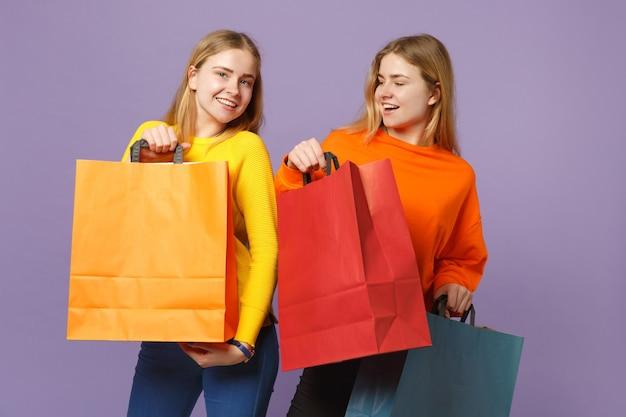 Due giovani sorelle gemelle bionde gioiose in abiti vivaci che tengono la borsa del pacchetto con gli acquisti dopo lo shopping isolato sulla parete blu viola. concetto di stile di vita familiare di persone.