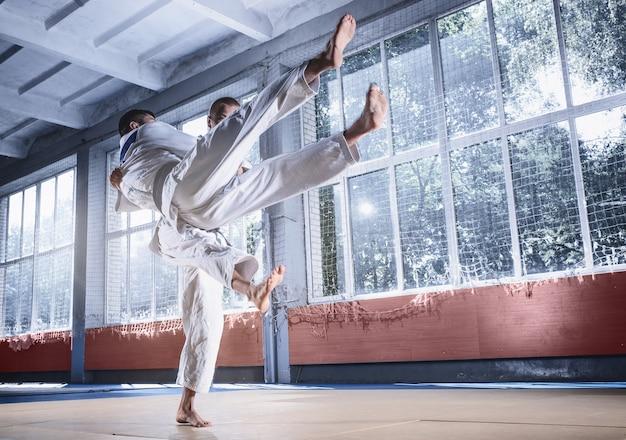 Due combattenti di judo che mostrano abilità tecniche mentre praticano arti marziali in un fight club. i due uomini in forma in uniforme. combattimento, karate, allenamento, arti, atleta, concetto di competizione