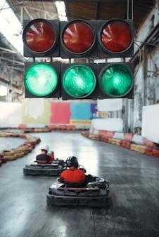 Due piloti di kart iniziano la gara, semaforo verde