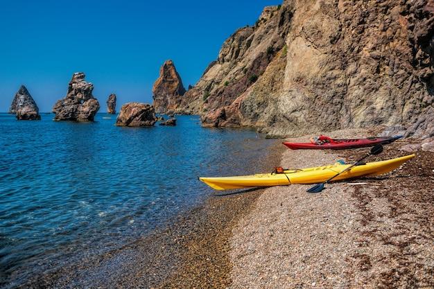 Due kayak su una spiaggia rocciosa isolata di una scogliera nel mare. kayak lungo la costa dell'isola vicino agli scogli. il concetto di una vita attiva in armonia con la natura.