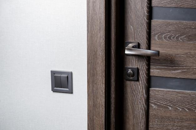Interruttore a due chiavi di colore grigio vicino alla porta, interruttore meccanico in plastica. l'interruttore della luce viene installato dopo la riparazione. concetto di risparmio energetico. chiudere l'interruttore della luce