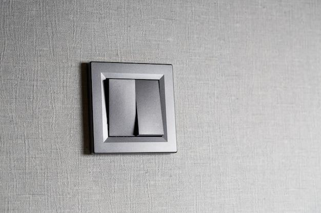 Interruttore a due chiavi grigio sulla parete un interruttore meccanico in plastica. interruttore della luce installato dopo la riparazione. il concetto di risparmio energetico. primo piano dell'interruttore della luce con copia spazio a lato