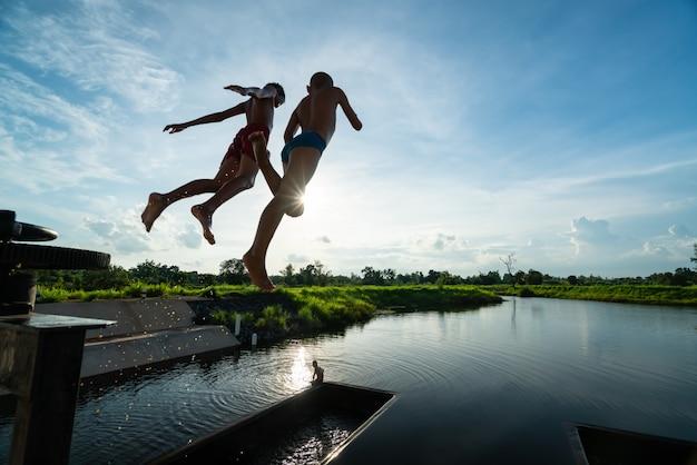 Due bambini in aria mentre saltano nel lago con un bel raggio di sole