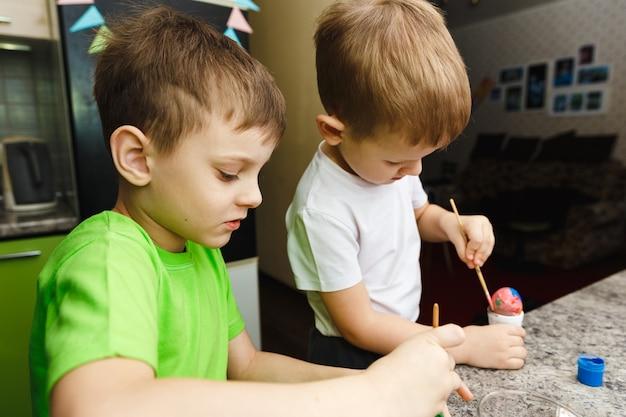 Due bambini preparazione pasquale dipingendo uova di pasqua e decorazioni natalizie a casa
